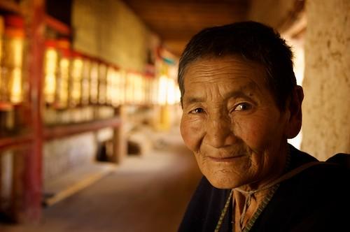 This elderly Tibetan woman is taking a break from walking koras - circles walked around religious monuments.  Dawu (Dafu), Tibet (China).