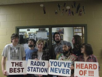 WMWC staff pose front of the station in the Woodard Campus Center. From left: Will Loring, Andrew Allingham, Sarah Kelly, Jeremy Lay, Joe Calpin, Connor Whitaker and Emily Harris.