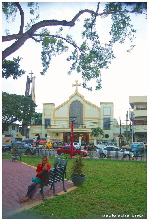 An old promenador rests on a bench with the Our Lady of Peace and Good Voyage Church on the background.