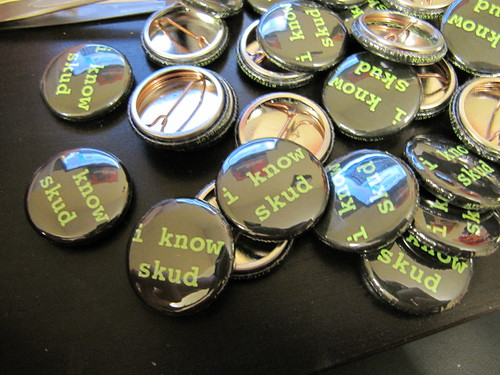 a pile of conference buttons emblazoned with I KNOW SKUD