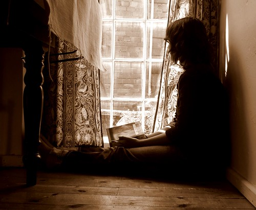photo of a girl sitting the floor staring out a window while holding a book