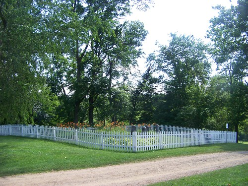Entire cemetery surrounded by white picket fence