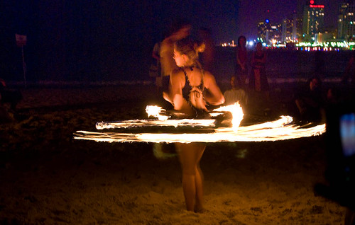 Some girl wearing an interesting outfit dancing around with fire.