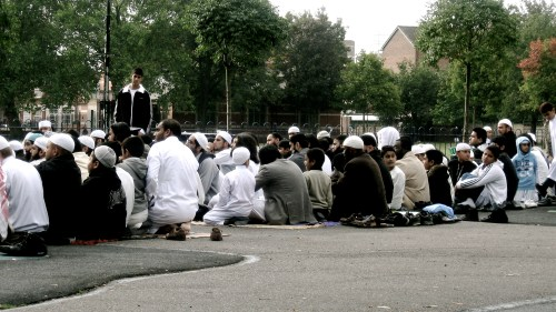 The brothers sit and listen to the imam.