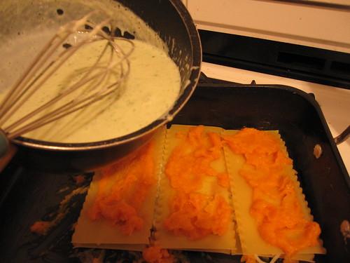 pouring the pesto béchamel over the butternut squash lasagna