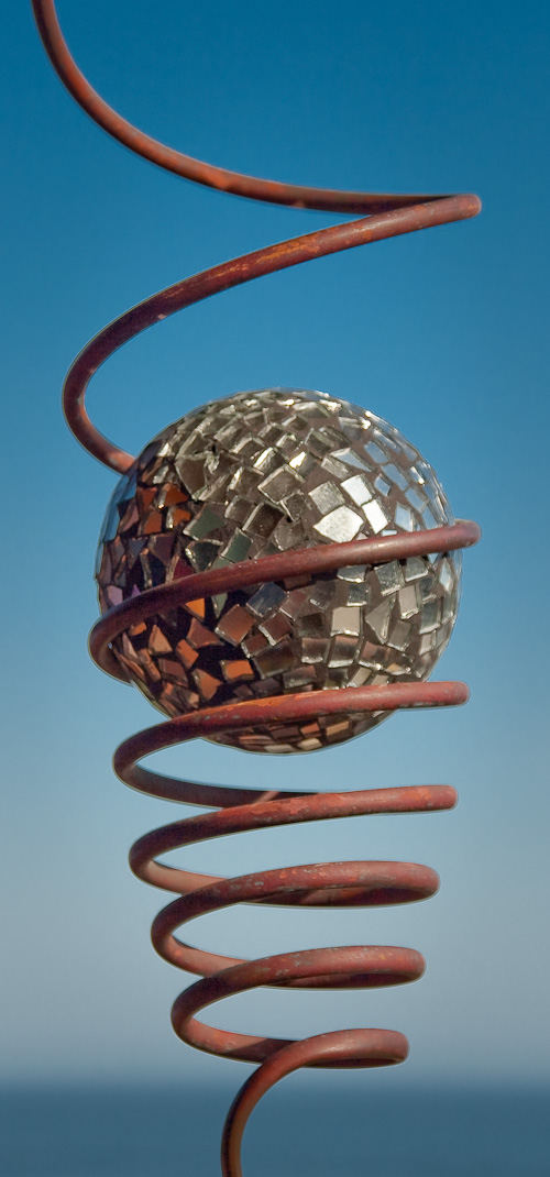 An art work of a mirrored ball suspended in a metal spiral, depicted against a backdrop of blue sea and sky.