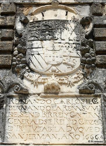 Escudo e inscripción en piedra en el Portal de San Nicolás, situado en los Jardines de la Taconera
