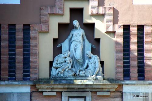 Grupo escultórico en la puerta de acceso a la «Casa de Misericordia», en la Vuelta del Castillo, obra del arquitecto pamplonés Víctor Eusa.
