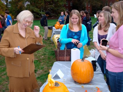 President Judy Hample judges this years crop of pumpkins while students look on.