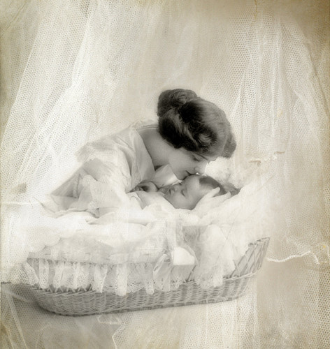 Mother tenderly kissing forehead of her infant baby sleeping in a bassinet