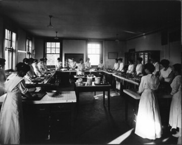 Foods laboratory in home economics building (now Comstock Hall) in October 1917. Instructor appears ...