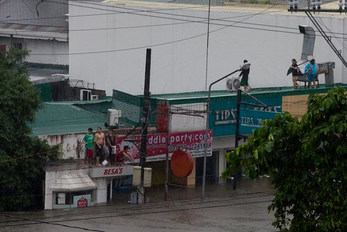 Residents and workers take refuge on rooftops as water rises at Barasoain and Wilson Street in Little Baguio in San Juan City.  Located at a hilly part of the metro, residents and local offiicials were caught unprepared by the rising water in the area.  Residents said that it was the first time they saw the creek overflowed that way.