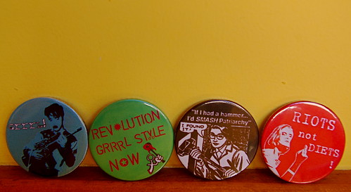 Photo of 4 badges, left to right - blue with 'grrrl' and image of a woman holding a gun, green with 'Revolution grrl style now', black with text saying 'IfI had a hammer I'd smash the patriarchy' and cartoon  of woman holding a hammer marker 'Feminism', red with 'Riots not diets' and image of woman with her middle finer raised.