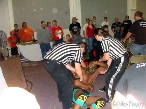 Referees help Ruddick to the back after he was smashed through a table courtesy of the new HVW Heavyweight Champion, Kahagas. Photo by Kari Williams