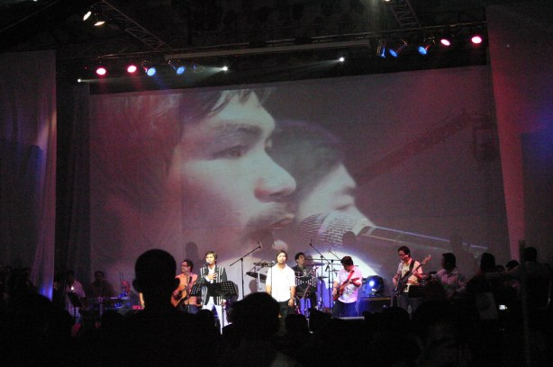 """A GIANT SCREEN SHOWS THE LIVE FOOTAGE OF MANNY PACQUIAO AND COMPOSER LITO CAMO PERFORMING ON STAGE.  BOTH SANG ABOUT 15-20 SONGS."""