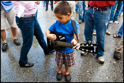 Four-year-old Reid Boyd of Columbia plays his guitar while listening to James Hand on Saturday, Sept. 26, 2009, at the stage at Seventh and Locust Steets. Boyd, who doesnt know chords yet but can pick out tunes by watching others, is on his third guitar.