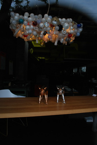 Light display hanging over one bronze pig and  one silver pig