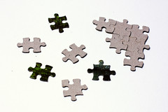 """Scattered puzzle pieces next to solved fragment"" by Horia Varlan on Flickr"