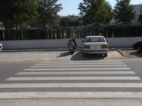 El vado de peatones que permite el acceso a la entrada Este del Leonardo Da Vinci desde la piscina acaba en un aparcadero de coches