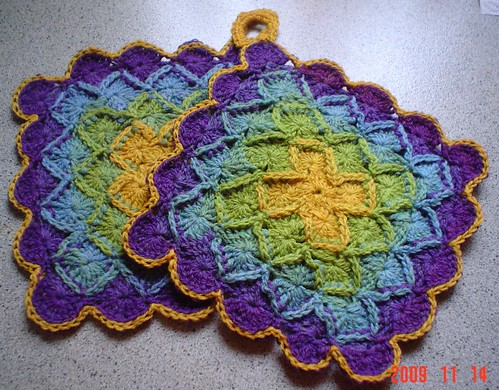 Two square potholders in morning glory colors: purple, sky blue, gold
