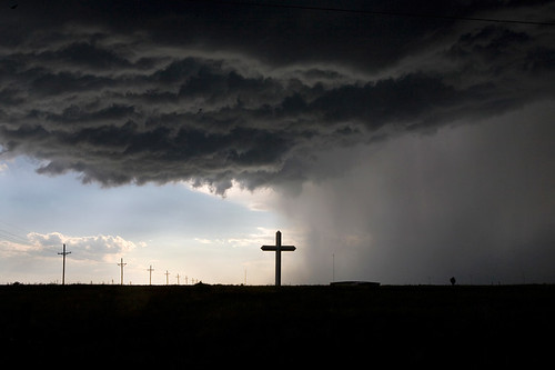 "On the final leg of a six-week United States of America road trip, I was driving east across Interstate 40 when a spot storm with golf ball-sized hail struck. A sign near Groom, Texas, announcing the ""largest cross in the western hemisphere"" explained the large crucifix Id been wondering about for miles on the highway; it seemed like an OK place to wait out the storm. On my way to getting stuck in the mud and a giant double rainbow, I saw this silhouetted view of the cross, splitting the sunny sky from the stormy plains. (Photo and caption by Brad Maule)"