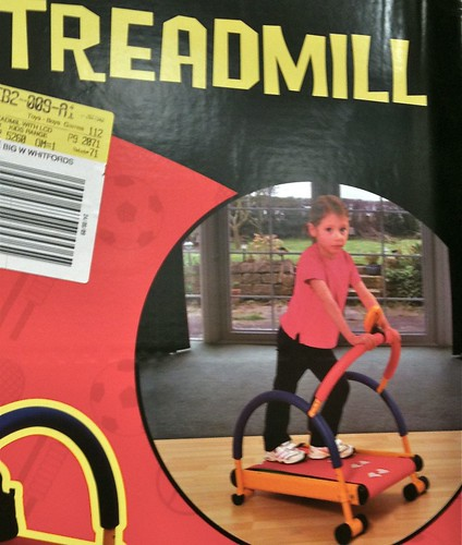 toy package marked TREADMILL. A sad, resentful-looking girl in exercise gear, around kindergarten age, stands on the treadmill