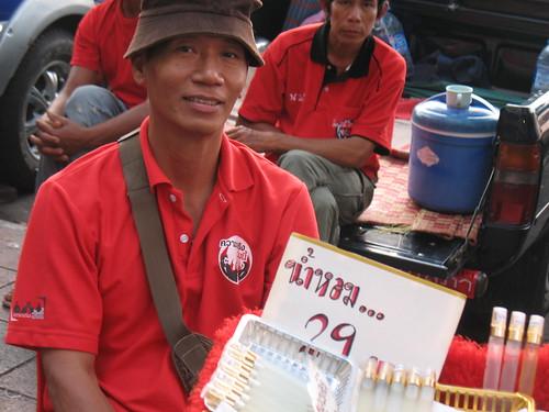 Red shirt vendor selling perfumes