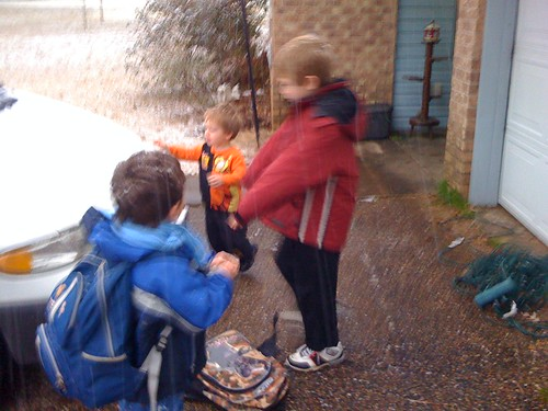Kids making snowballs out of snow accumulated on van