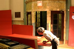 Irene Lawrence helps by touching up the paint on the wall panels prior to installation.