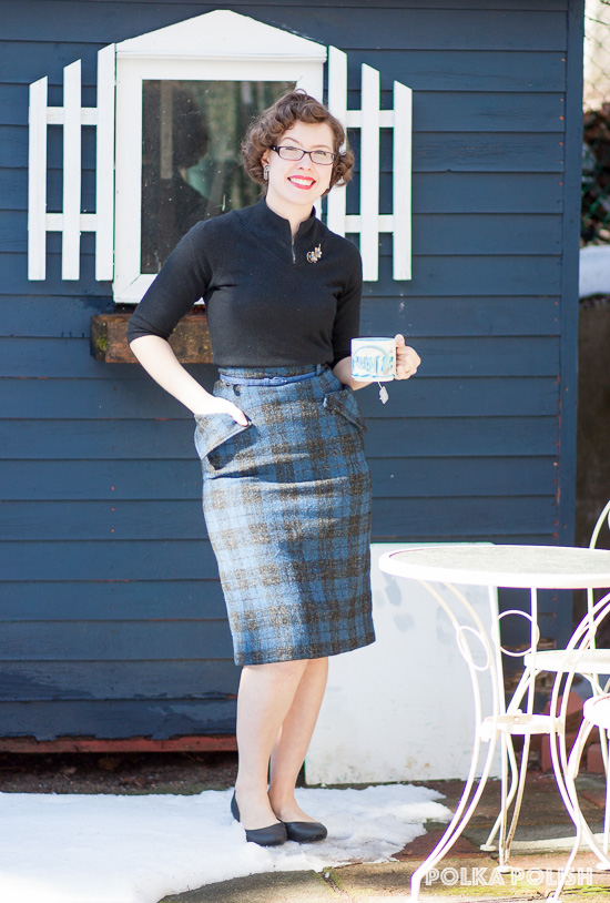 50s inspired low-key workwear outfit with a black sweater and a blue plaid skirt with huge hip pockets