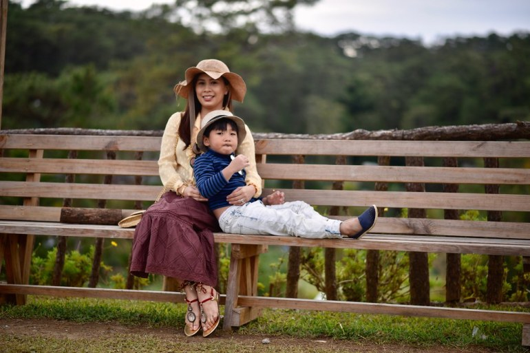 mother and son on a bench at the Baguio Country Club