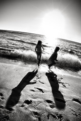 The long shadows of two girls on a beach