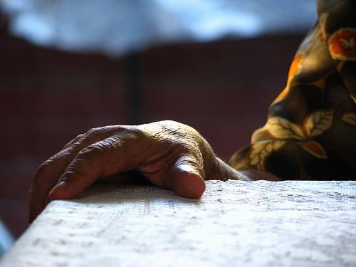 La mano de un anciano sobre una mesa