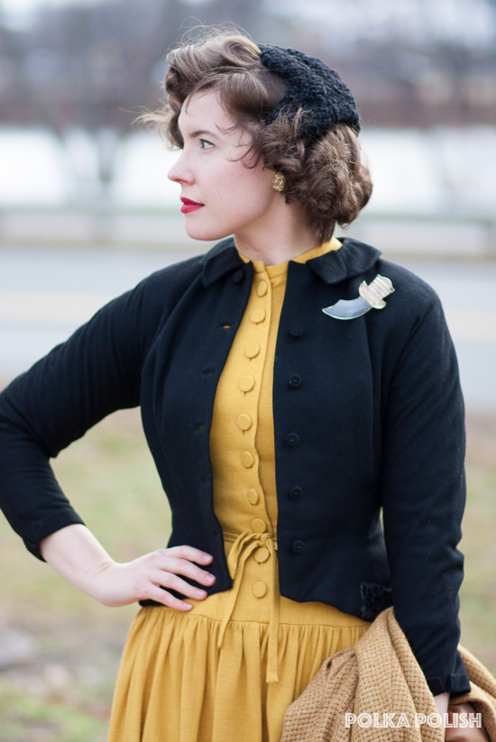 A goldenrod yellow vintage jersey knit dress with a row of buttons down the front is set off by a black blazer and a lucite large scimitar brooch