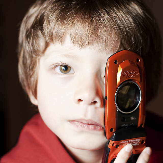 Photo of a child holding a cell phone