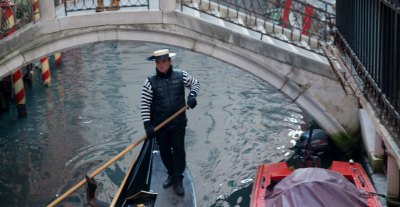 Gondolier rowing his gondola down a canal in Venice italy
