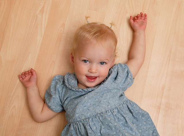 Playful toddler on hardwood floor