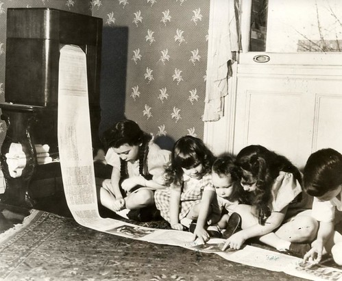 In 1938 the first wireless newspaper was sent from WOR radiostation in New York. Photo shows children reading the children's page of a Missouri paper.