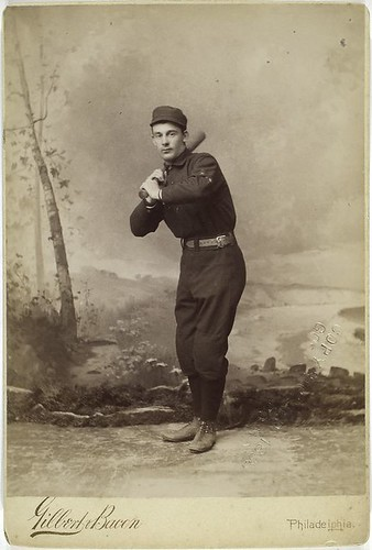 Unidentified baseball player in dark uniform - batting form.