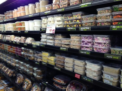 Shelves stocked with containers of prepared foods.