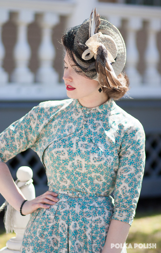 A New York Creations tilt hat with towering feathers is a perfect finishing touch with a vintage 1940s novelty print dress in shades of aqua and tan