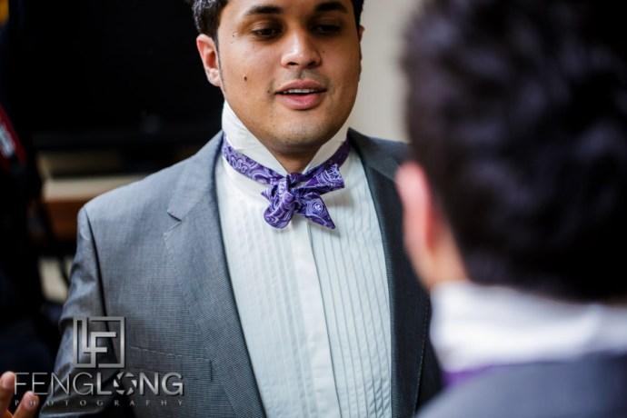 Groom tying a bowtie for his wedding reception