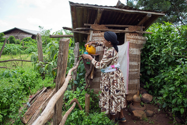 Kanu Fanta, 30, mother of 6, washes her hands at a latrine at her house