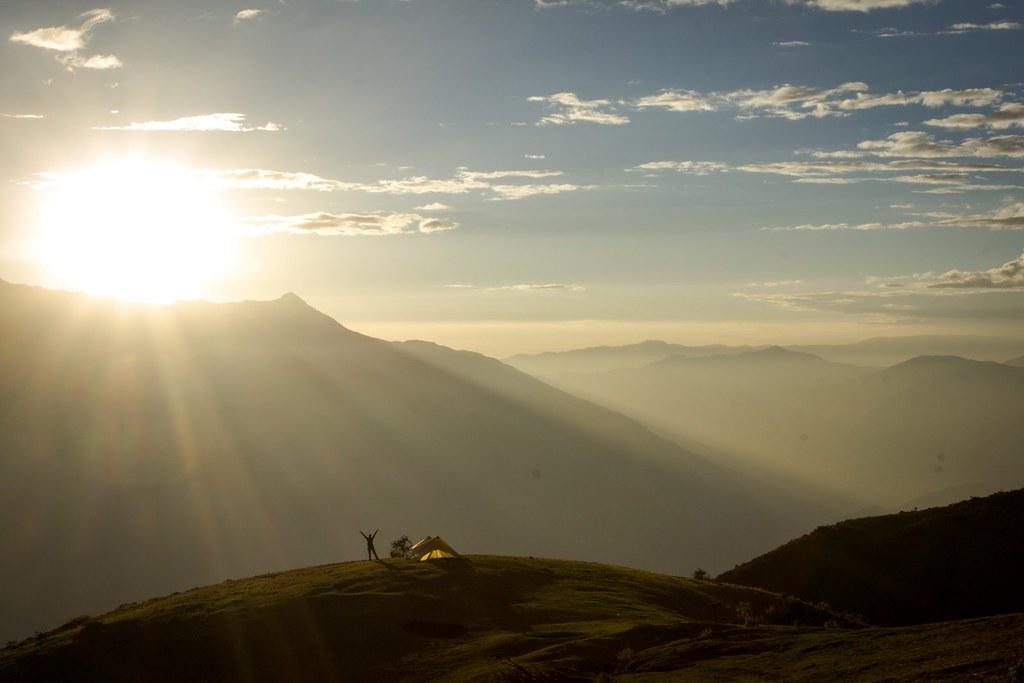Bivaouc high above the Callejón de Huaylas. Sun sets over the Cordillera Negra, the Blanca's icefree parallel range to the west. Huascaran National Park. Cordillera Blanca. Peru.