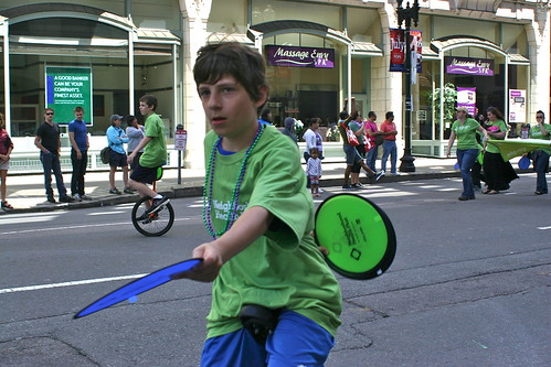 Boy on unicycle handing out fans