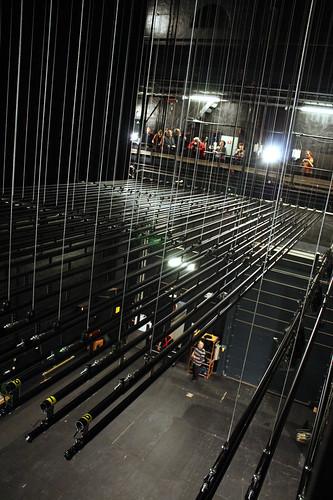 Halvvägs upp inramas rummet av smala bryggor. Det är många meter ner till scengolvet.