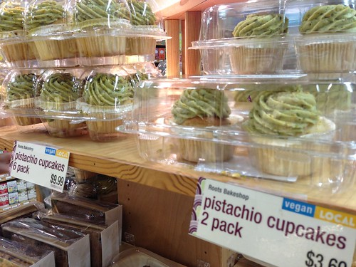 Packages of vegan pistachio cupcakes with abundant green frosting.
