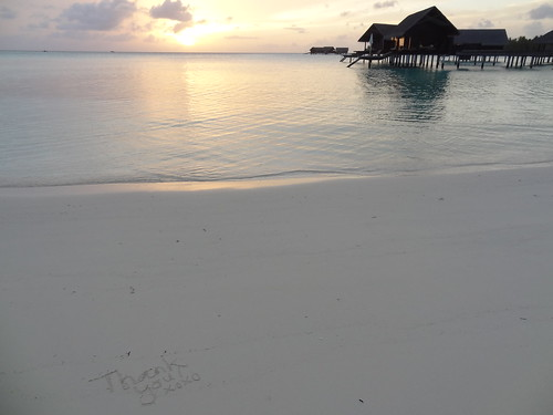 Sunrise on the beach looking out to the water villas