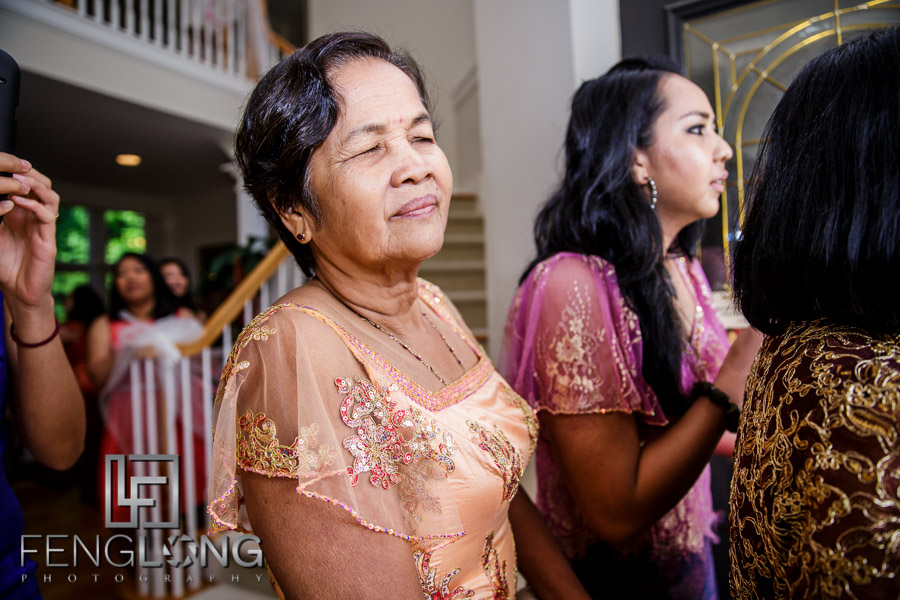 American groom offering gifts at Cambodian wedding processional