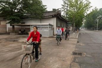 De mensen fietsen, lopen en bussen voorbij in de DPRK met een gezicht alsof er zojuist een dierbare is overleden.